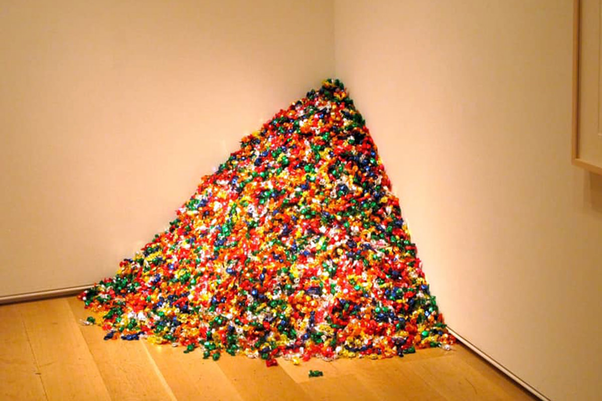 A corner in a white-walled art gallery. There is a large mound of multicolored candy piled up in the corner.