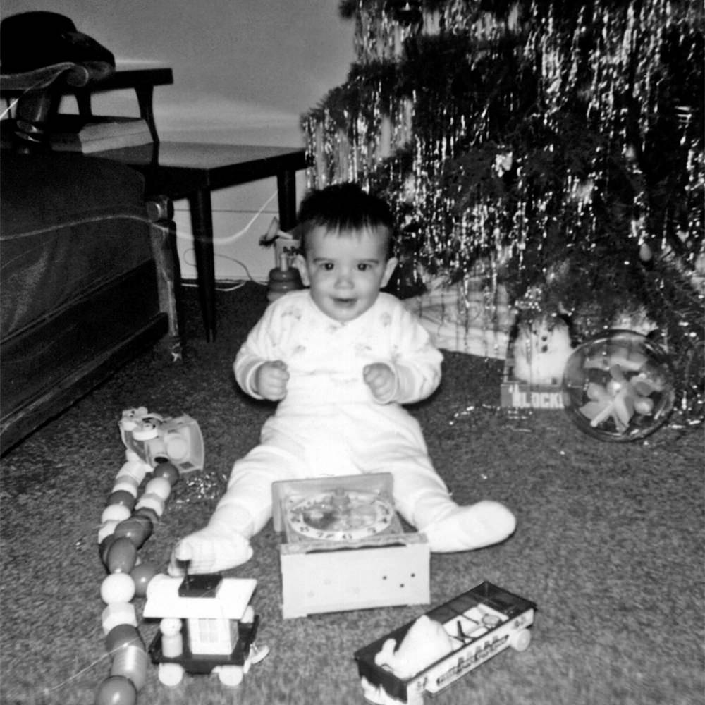 Young me sitting in front of a Christmas with a big present.