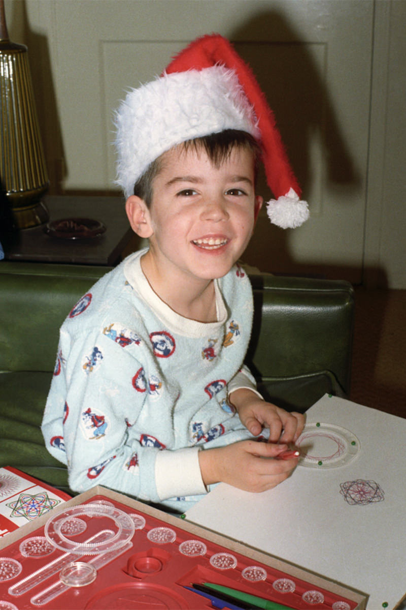 Young me playing with a Spirograph toy while wearing a Santa hat.
