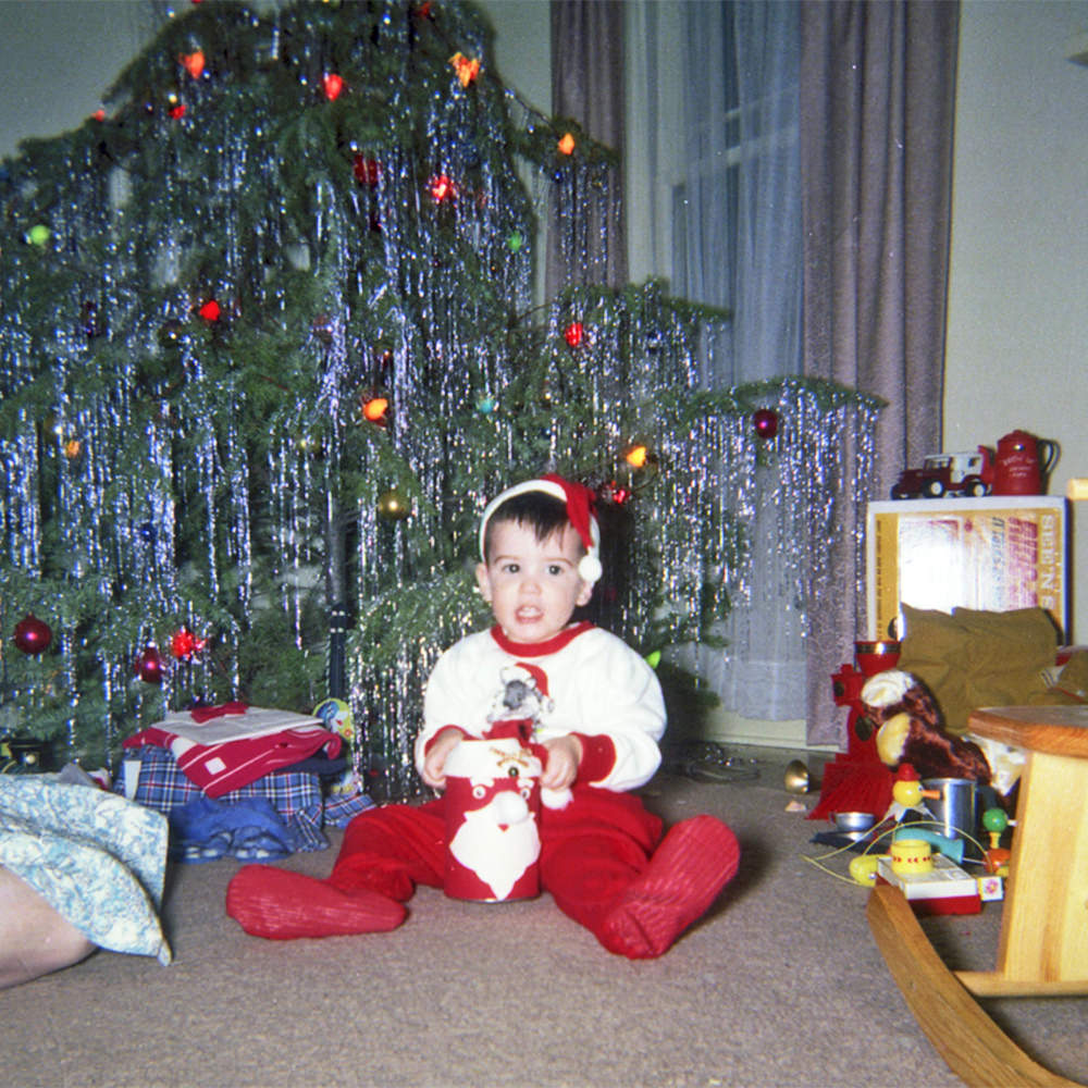 Young me sitting in front of a Christmas tree with Santa pajamas, complete with hat.