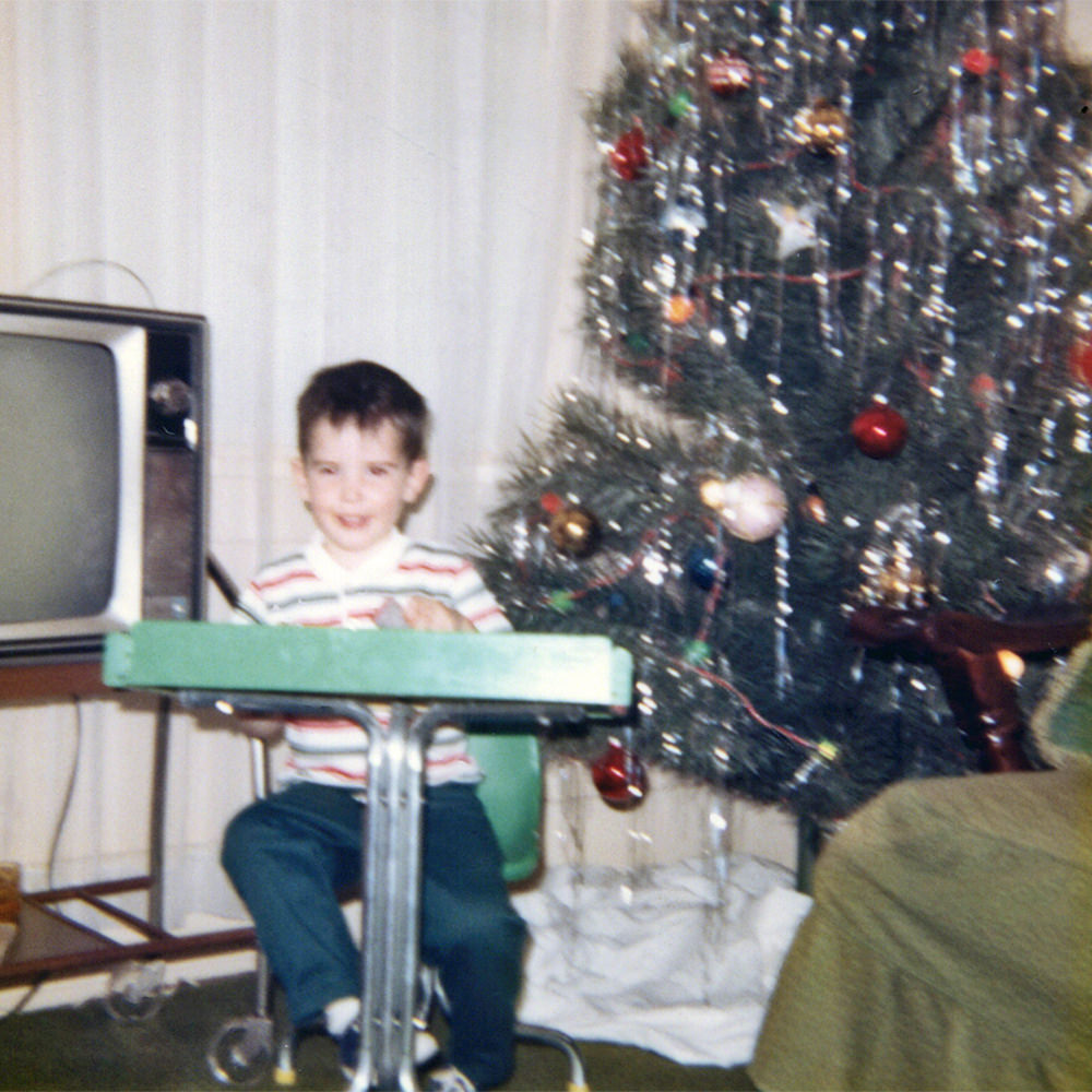 Young me sitting in a desk in front of a Christmas tree.