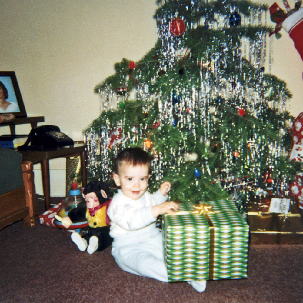 Baby me sitting in front of a Christmas tree with presents.