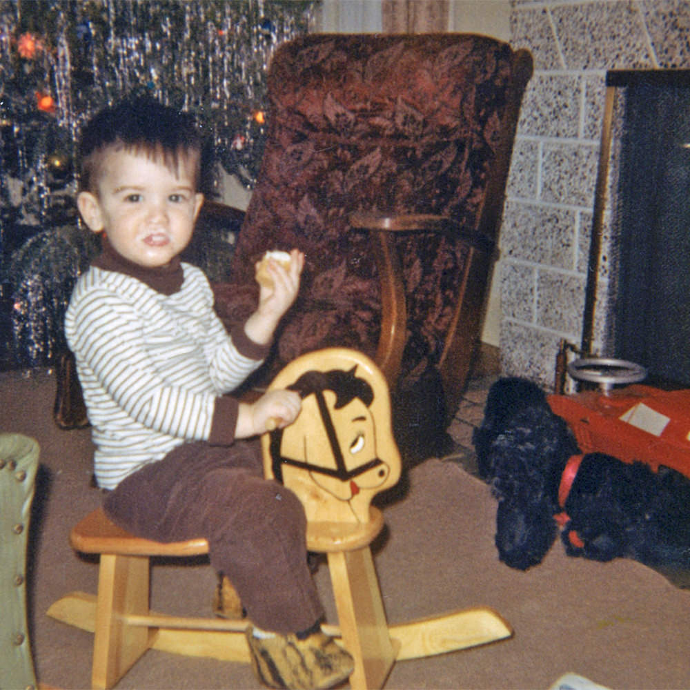 Young me sitting on a small rocking horse in front of a Christmas tree.