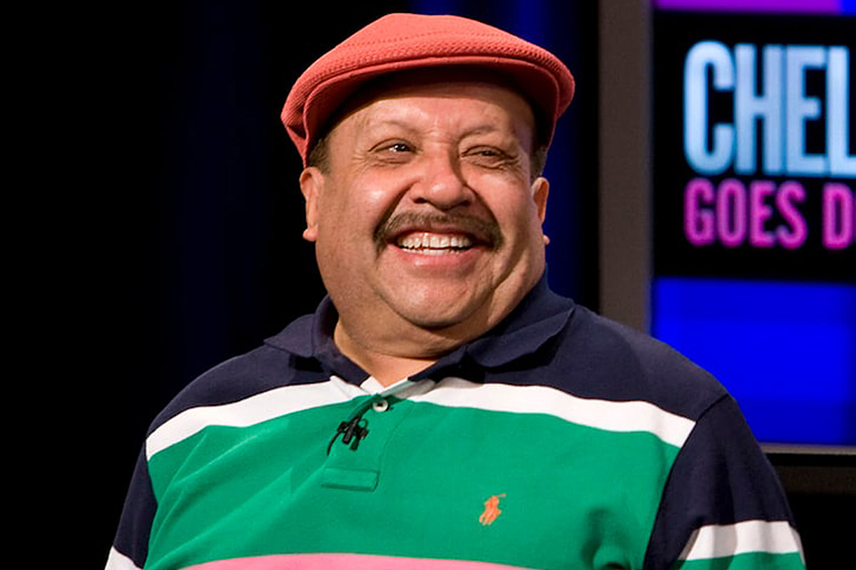 A photo of Chuy Bravo on the Chelsea Lately show wearing a cap and smiling.