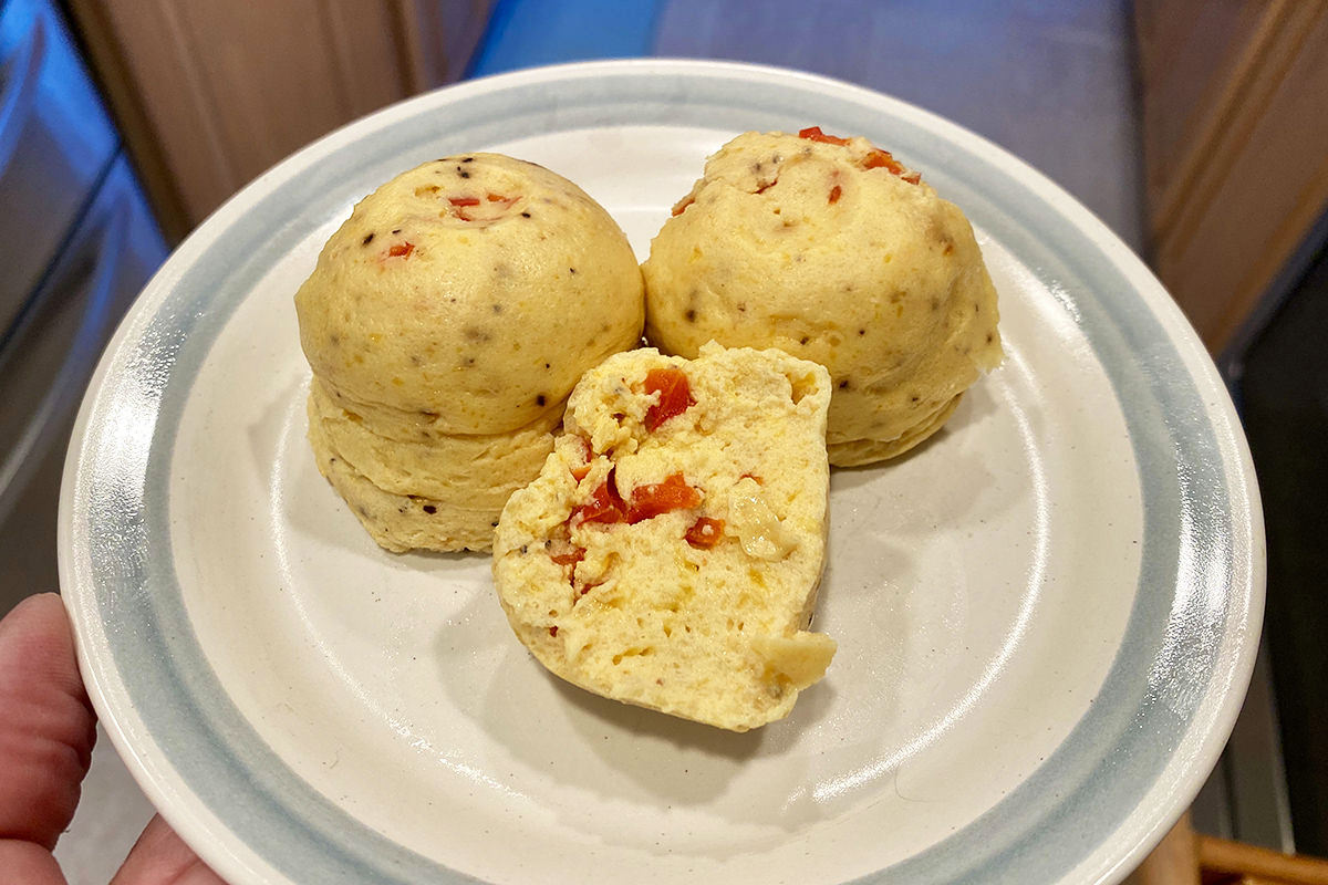 Egg Bites on a plate with one cut in half to show the red peppers inside.
