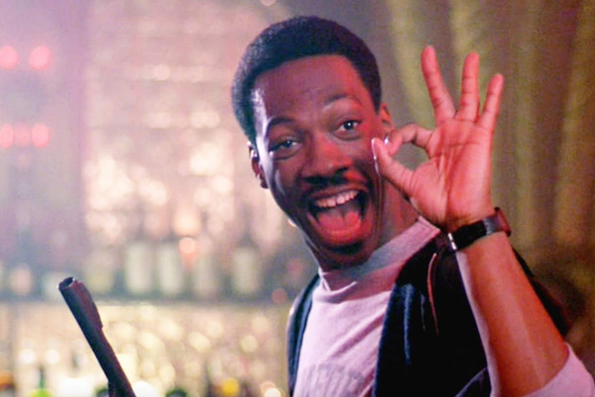 Eddie Murphy as Axel Foley from Beverly Hills Cop making the OKAY sign in one hand while holding a gun in the other.