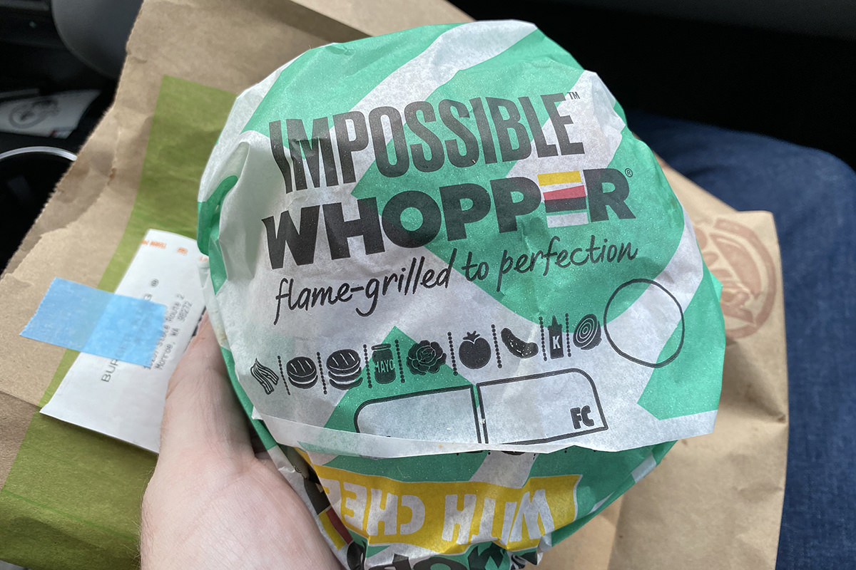An Impossible Whopper still in its wrapper on top of a Burger King bag inside a car.