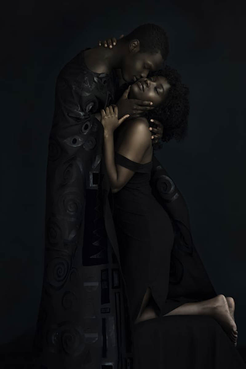 A Black couple reinacting the famous Klimt painting The Kiss.