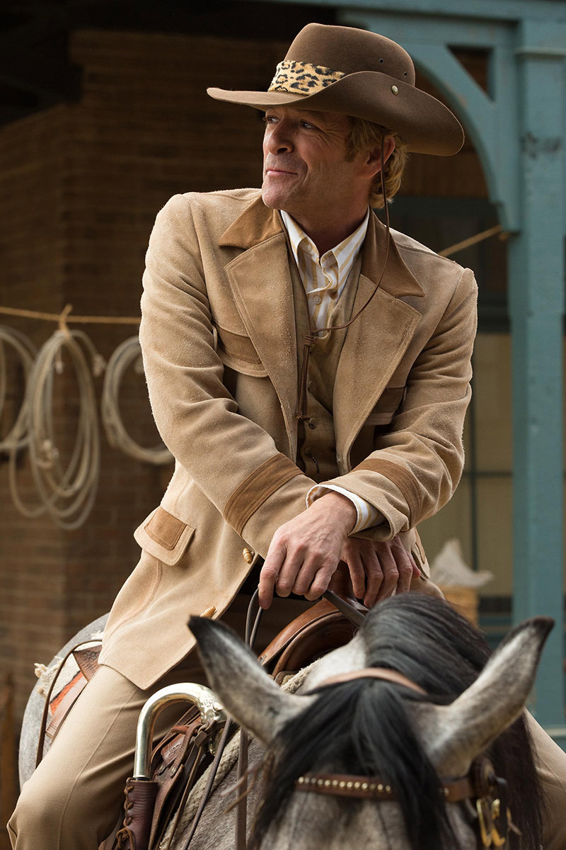 Luke Perry in Once Upon a Time in Hollywood on his horse dressed up in a Western suit complete with cowboy hat and leopard-print band.