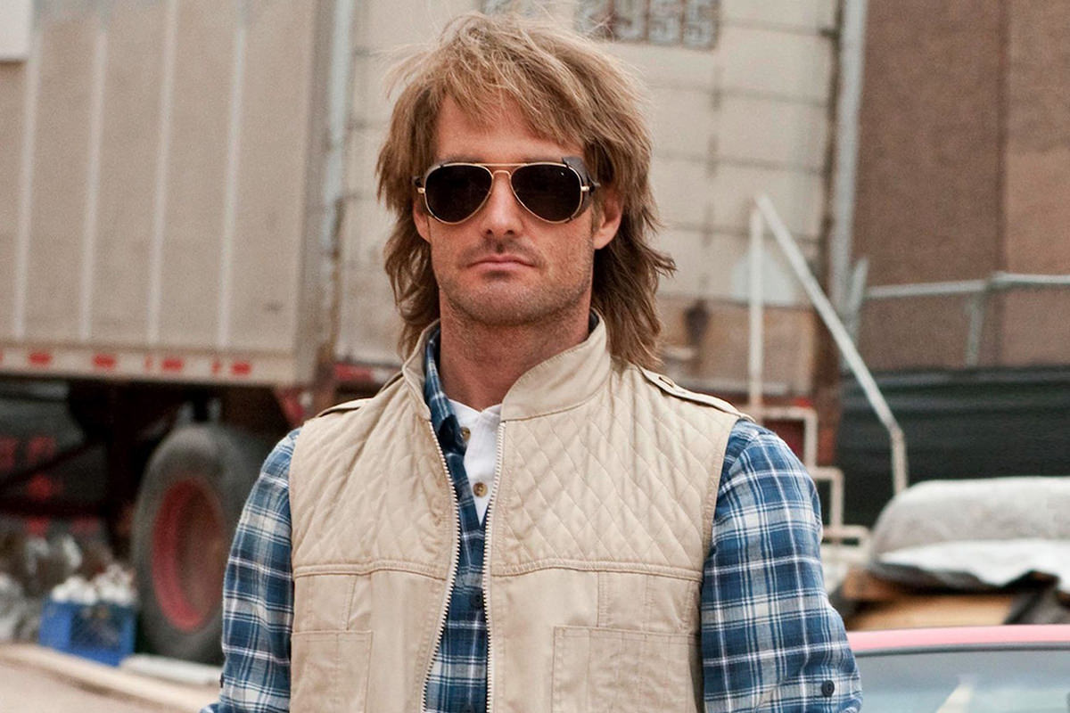 Will Forte as MacGruber wearing his trademark tan vest, plaid shirt, and sunglasses.
