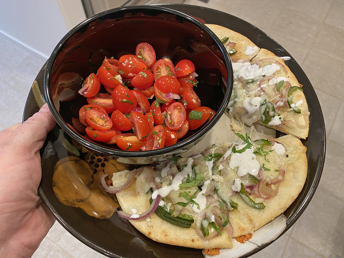My dinner. It's a pretty bowl of halved cherry tomatoes in a salad with flatbread pizza that has onions and poblanos and melted cheese..
