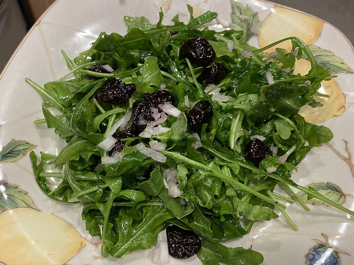My dinner, Part 2. It's a bowl of greasy arugula with dried cherries on top.