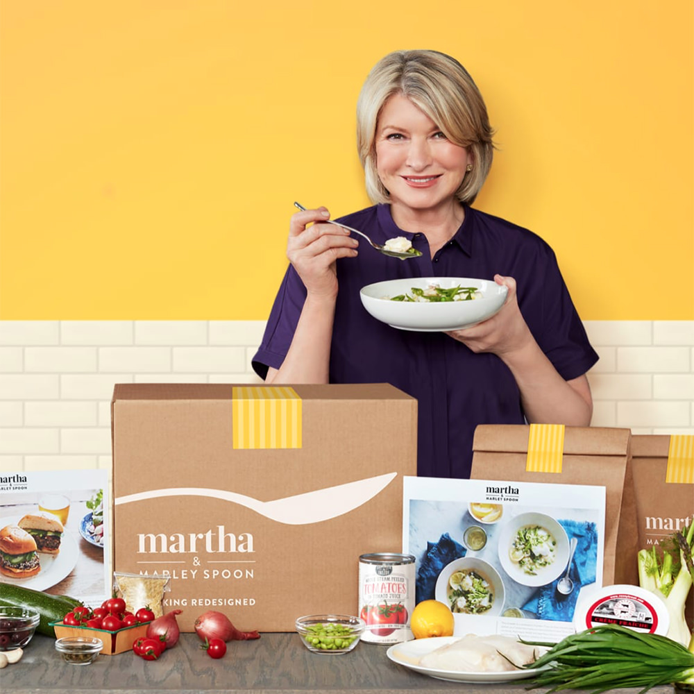 Martha Stewart eating a bowl of food in front of boxes of Marley Spoon stuff with ingredients in front.