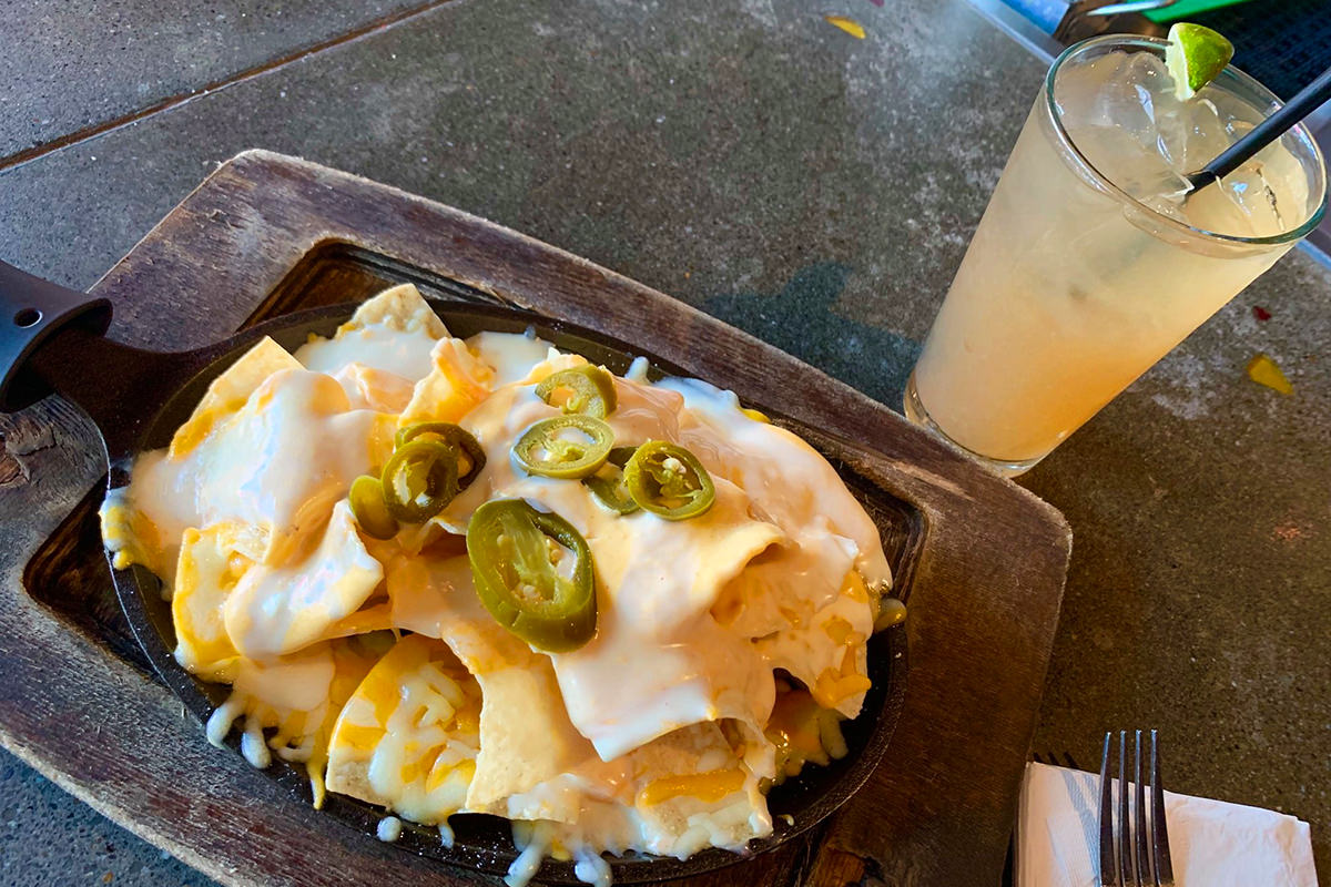 A plate of amazing-looking nachos sitting in front of a Long Island ice tea.