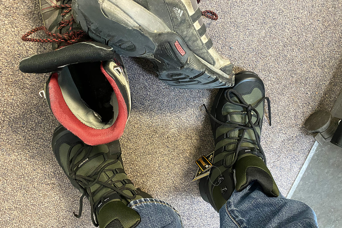 A photo of my new boots that look rugged in their forest green and balck... plus my old shoes which look nice except for the soles which are literally falling off the boot!