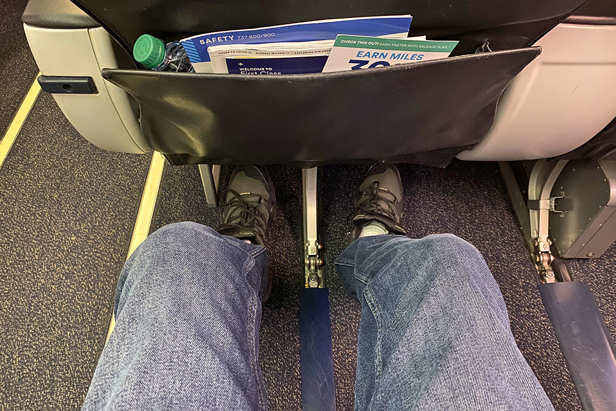 A photo of my legs stretching out in my First Class upgraded seat.