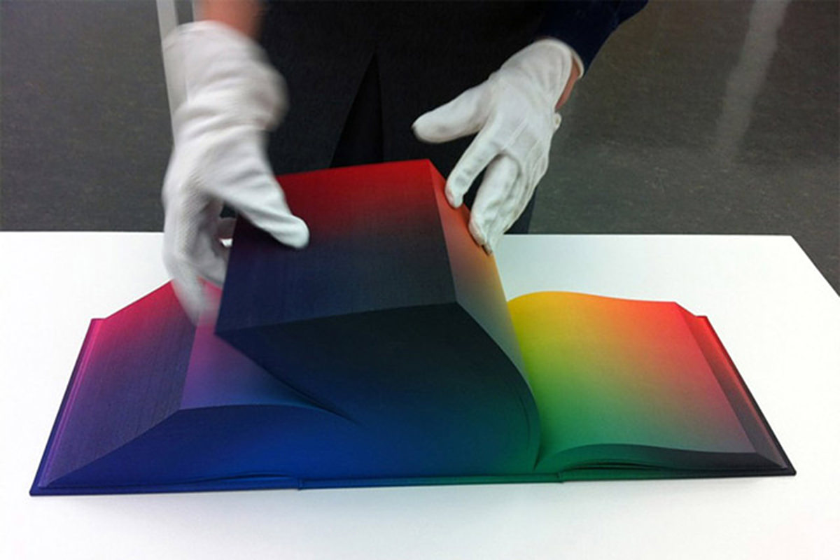 A person with white gloves turning the page of a massively thick volume of color pages in the RGB Color Atlas.