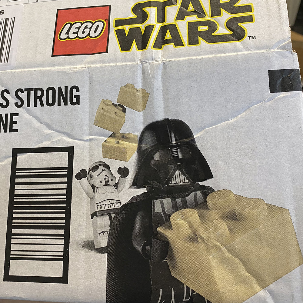 An Amazon box with LEGO Darth Vader using The Force to lift LEGO bricks over a LEGO Stormtrooper!