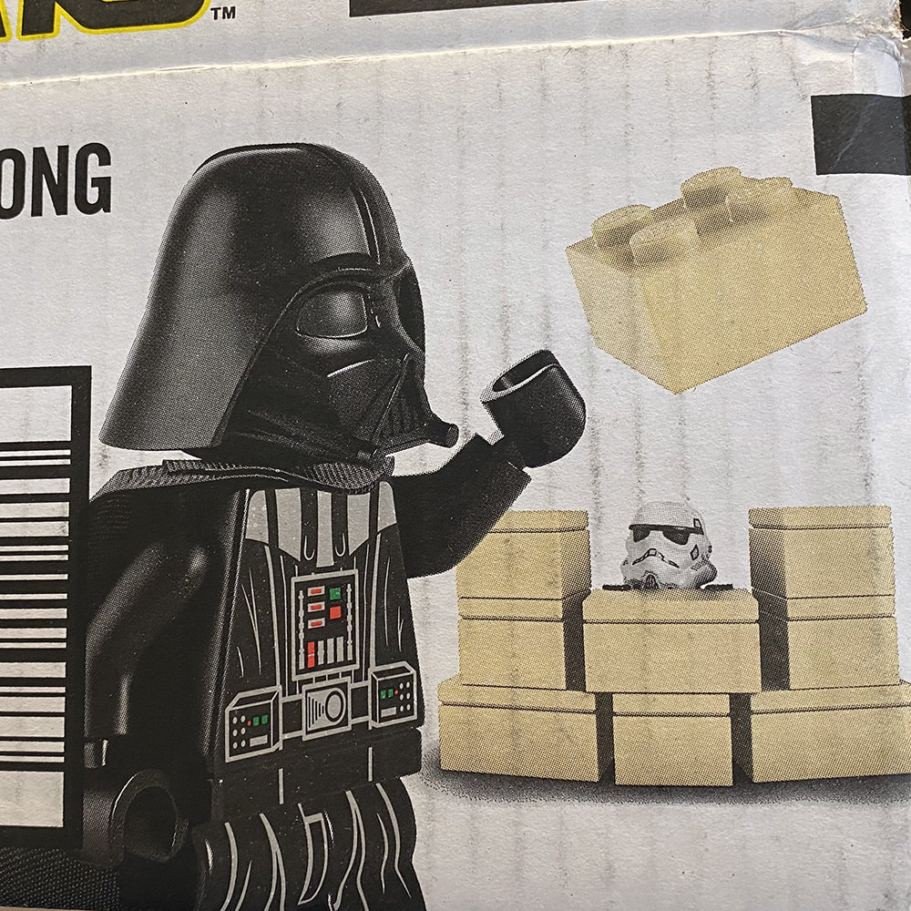 An Amazon box with LEGO Darth Vader has imprisoned the LEGO Stormtrooper in a jail cell made of the LEGO bricks!