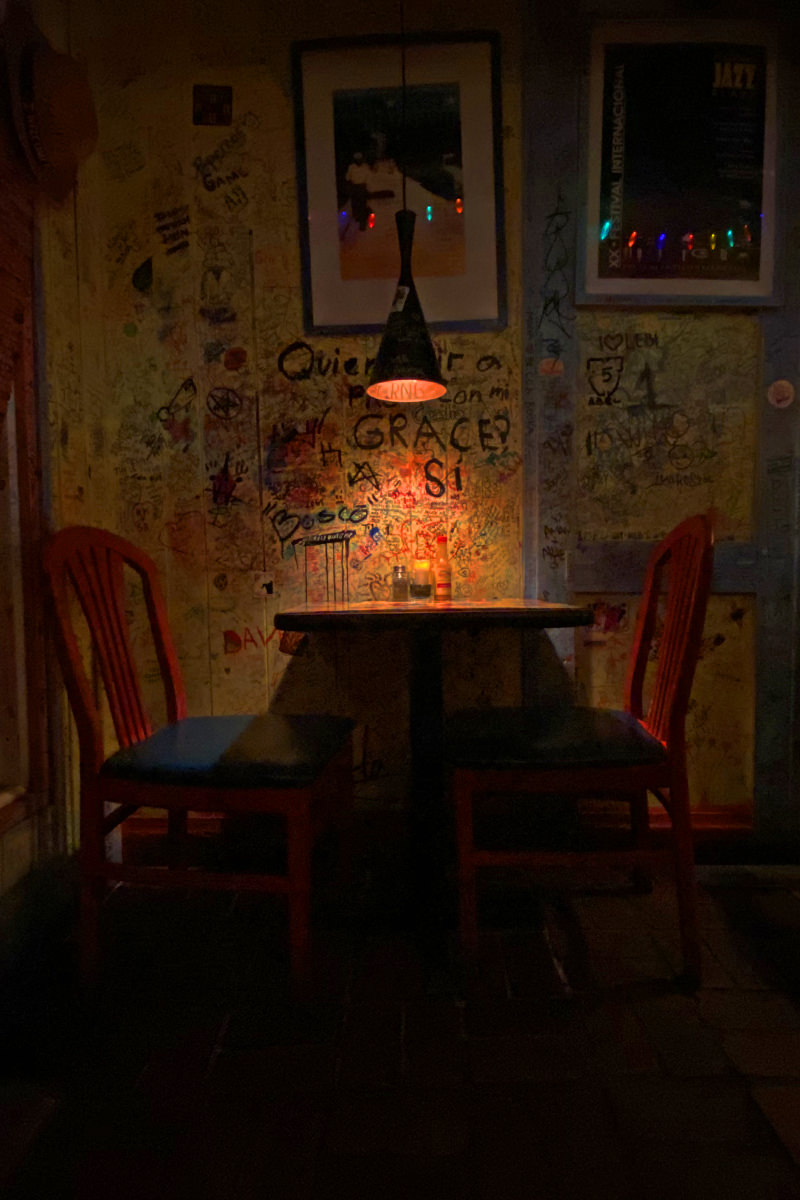 In a darkened corner of a small restaurant, a light above a small table illuminates grafitti-strewn walls as two brilliant red chairs sit empty.