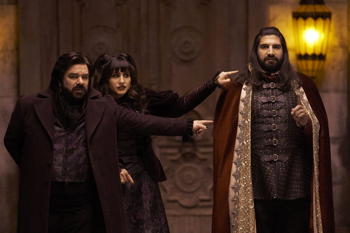 The TV cast for What We Do In The Shadows with two vampires pointing fingers at a third vampire
