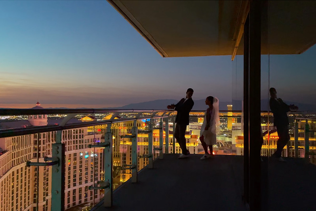 Video still of two people on a balcony overlooking Vegas.