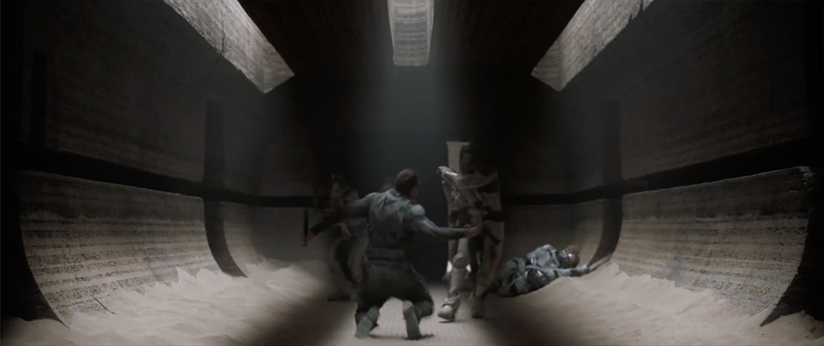 A large hallway in shadow with a fight happening in the middle, sand piled on the floor.