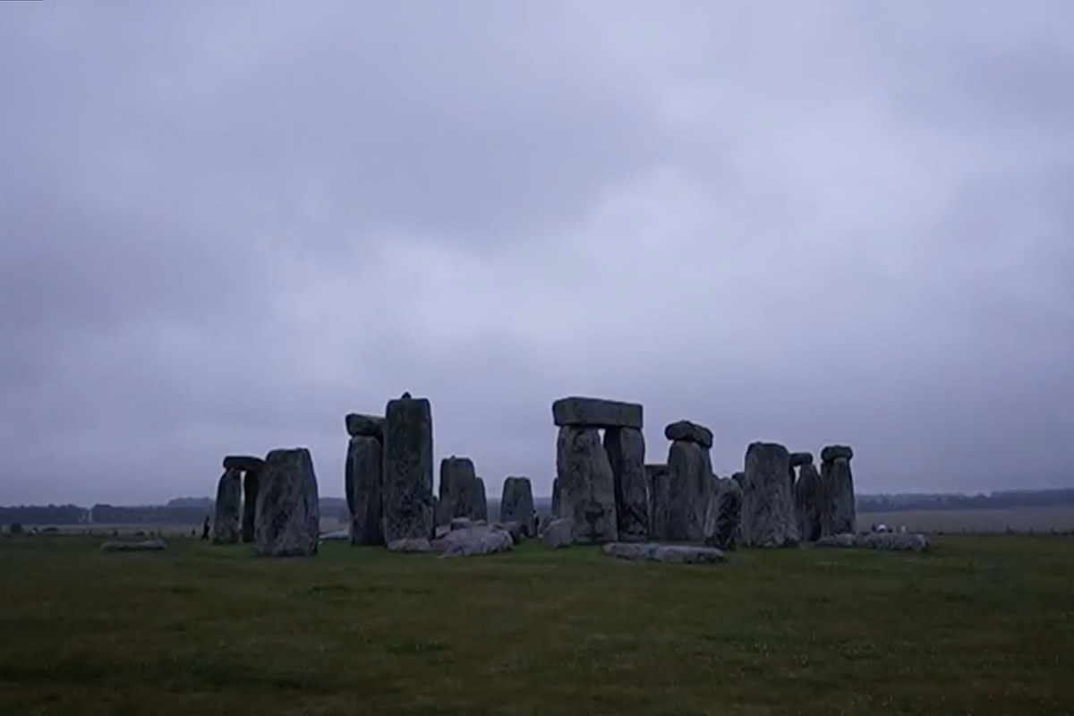 The giant stones of Stonehenge in heavy shadow as the sun has just set.
