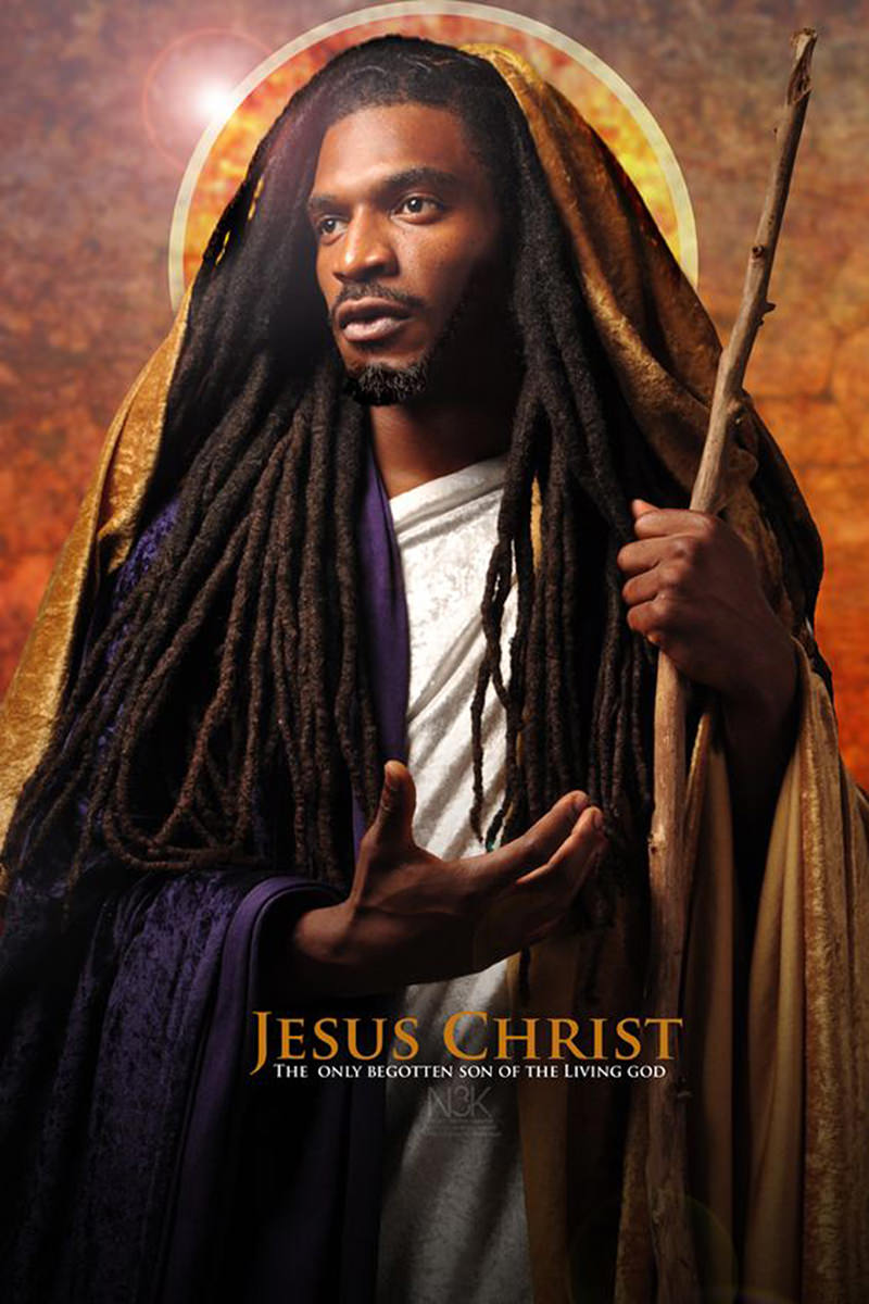 Black Jesus with long dreadlocks holding a wood branch as a staff with a halo behind his head as photographed by James Lewis.
