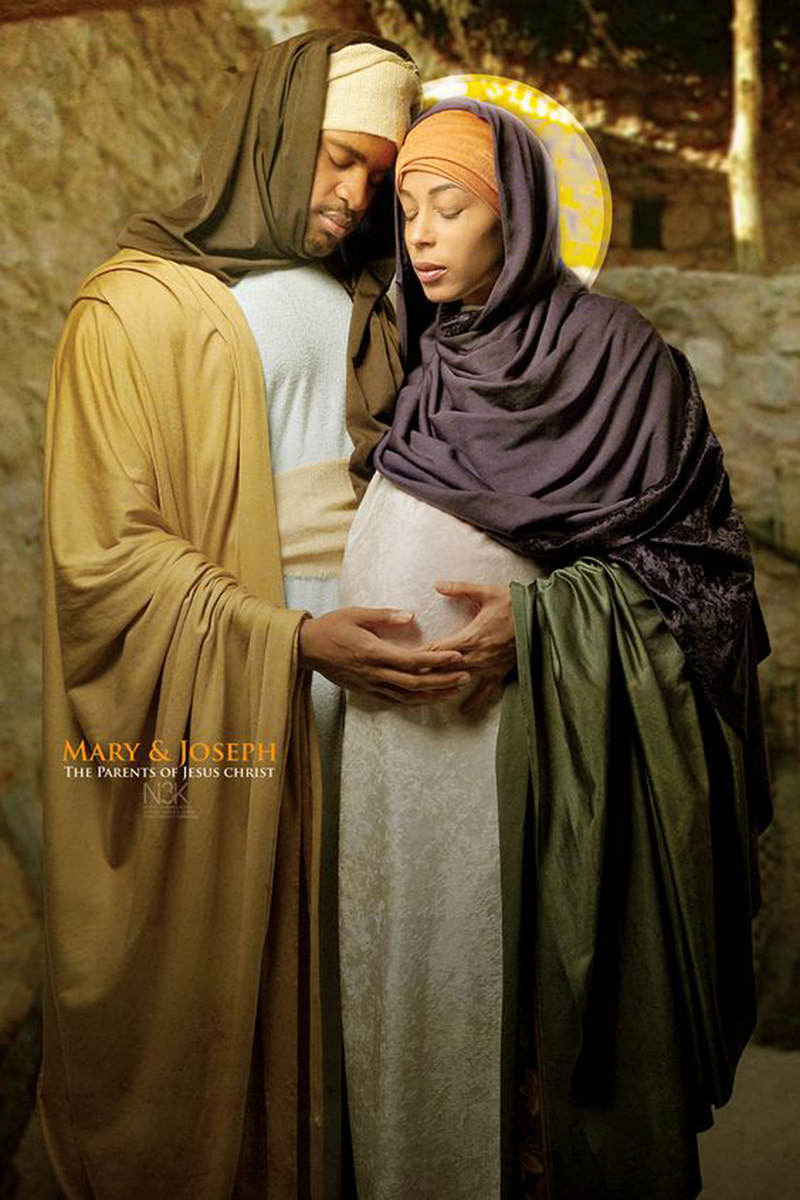 A pregnant Mary stands with a halo behind her head as Joseph lovingly touches her belly as photographed by James Lewis..