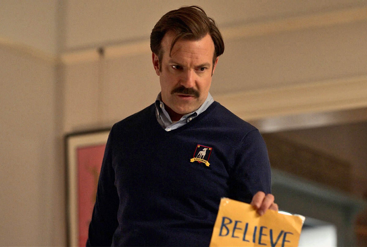 Ted Lasso holding up a handwritten sign that says BELIEVE.