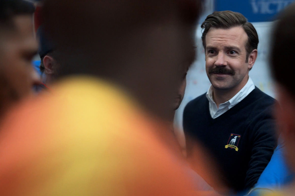 Ted Lasso smiling in a crowded locker room.