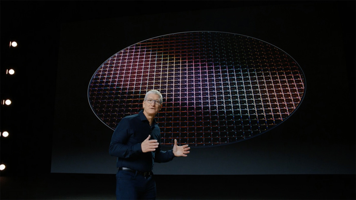 Tim Cook standing in front of computer chips on a big wafer.