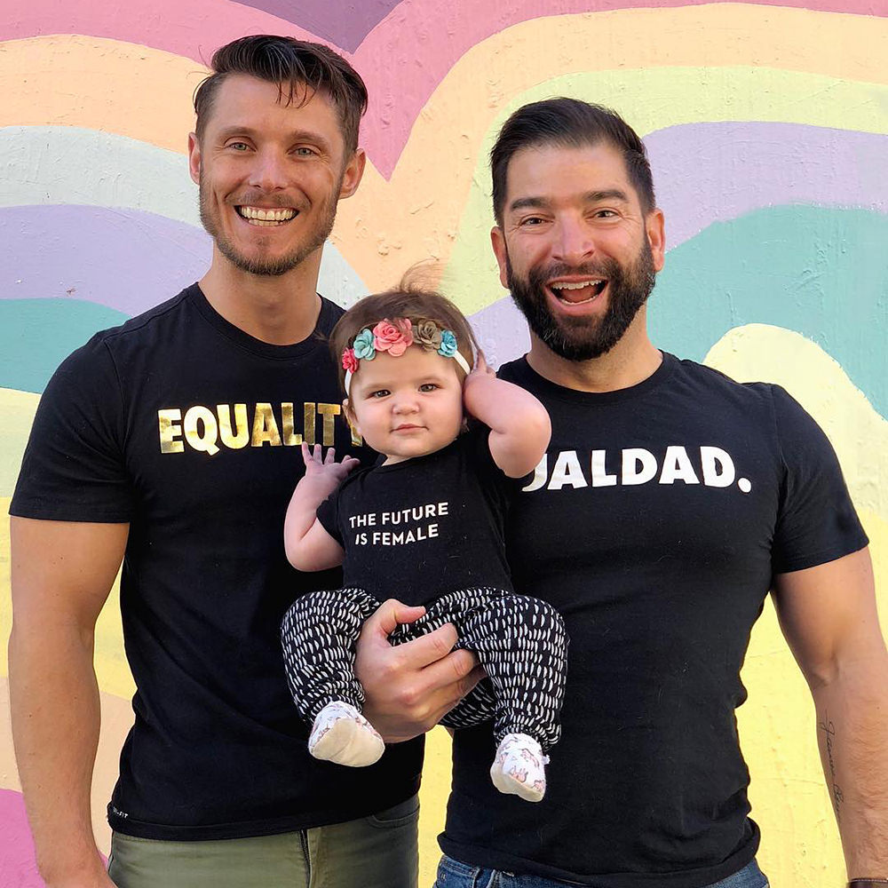 Two dads with their baby girl... who is wearing a T-shirt which says THE FUTURE IS FEMALE.