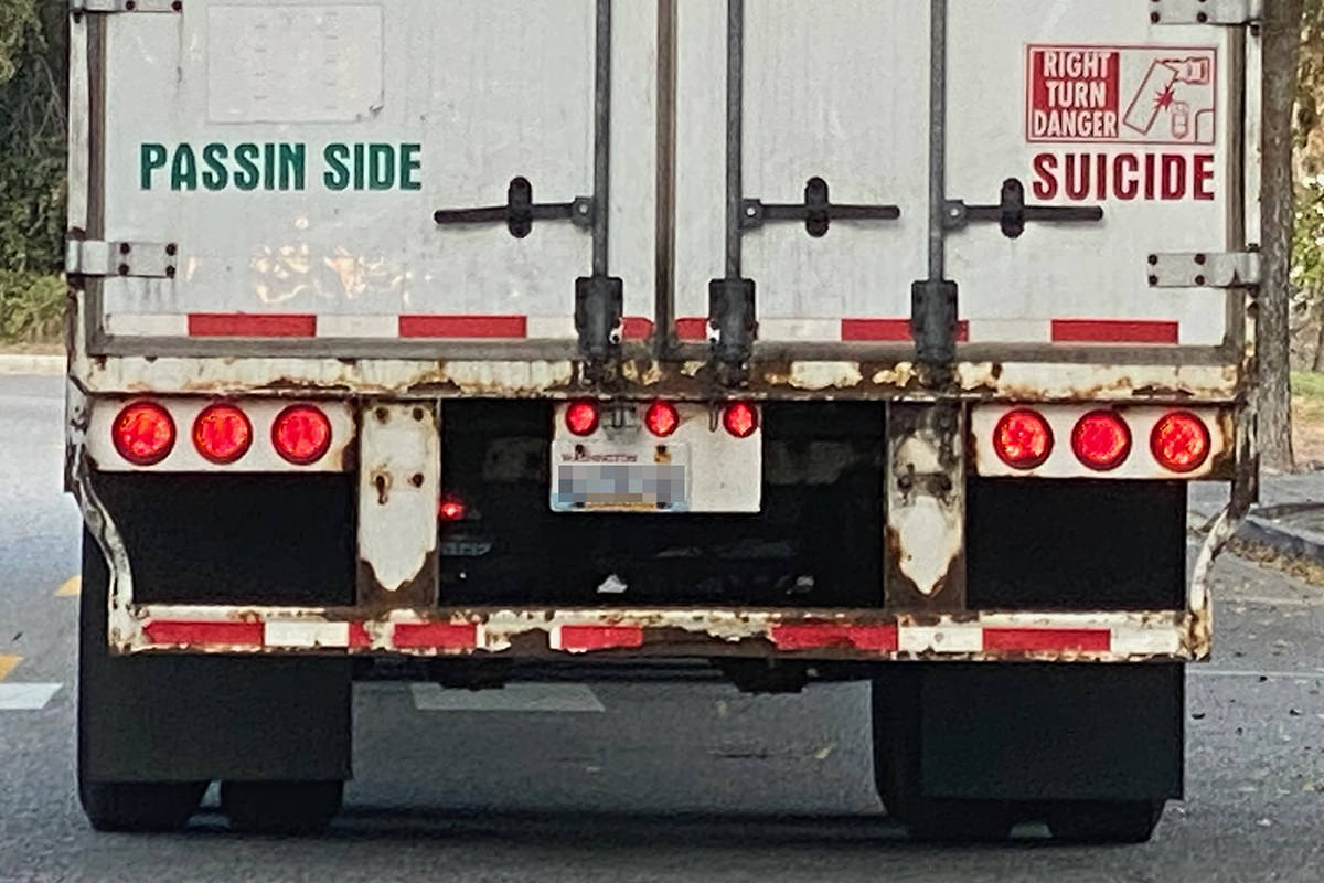 The back of a truck with PASSIN SIDE on the left and SUCIDE on the right.