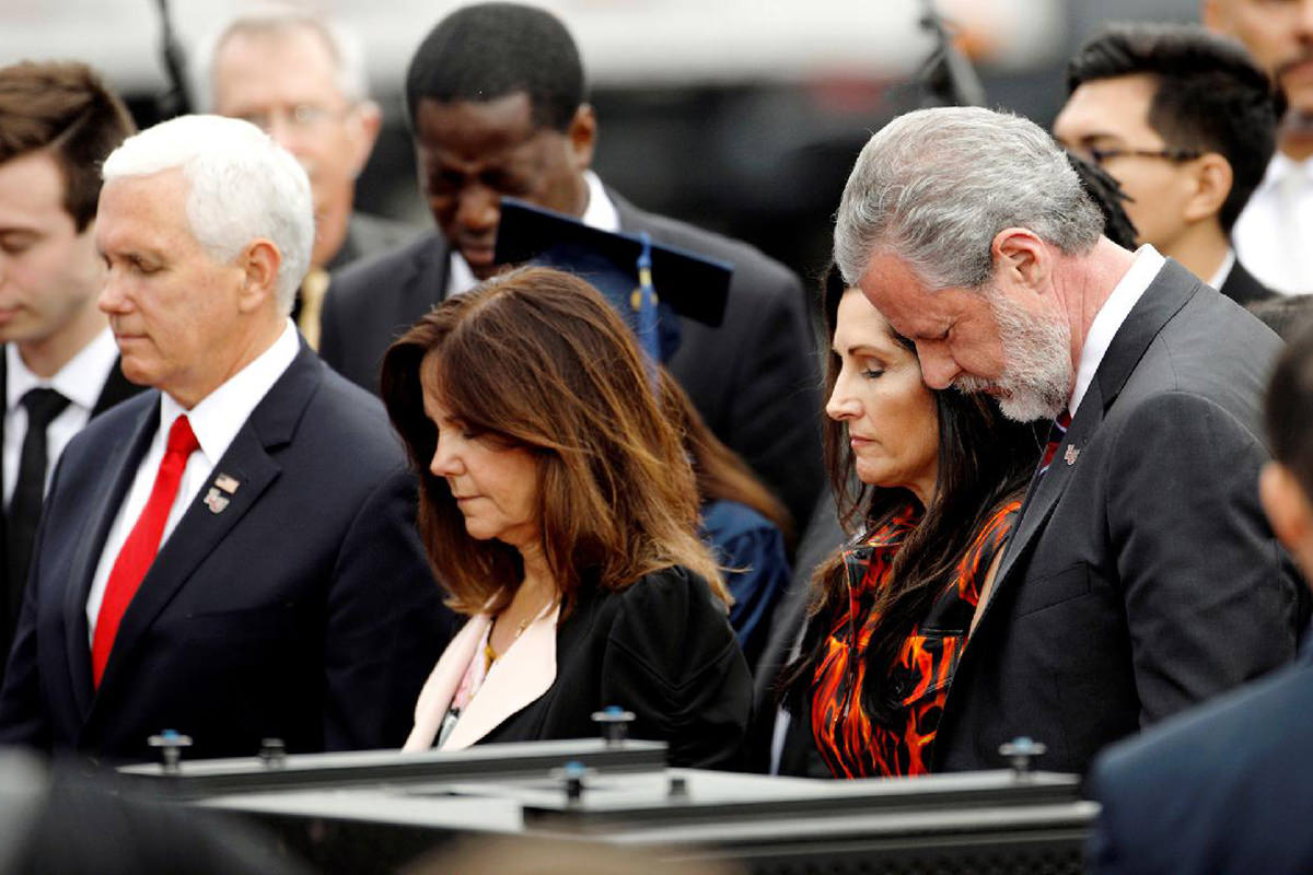 Vice President Pence and Jerry Falwell Jr. with their wives, their heads bowed in prayer looking like the assholes they are.