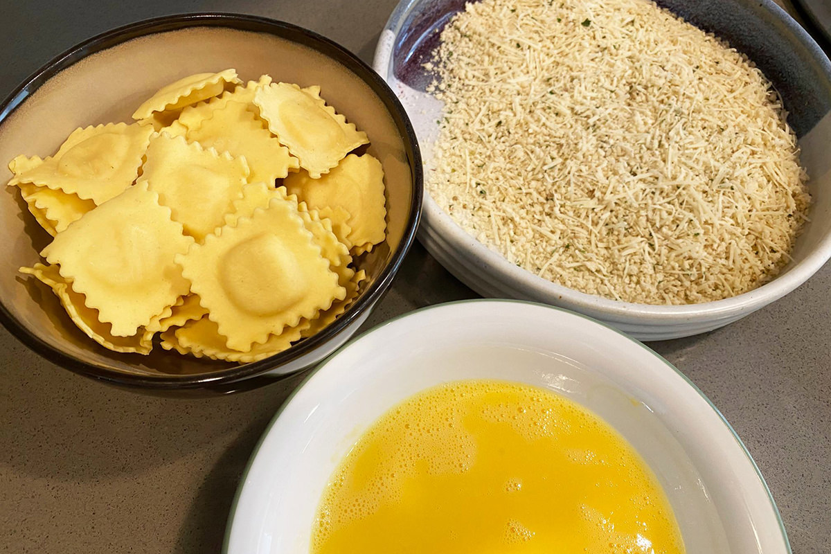 A bowl of small raviolis, a bowl of beaten egg, and a bowl of seasoned breadcrumbs.
