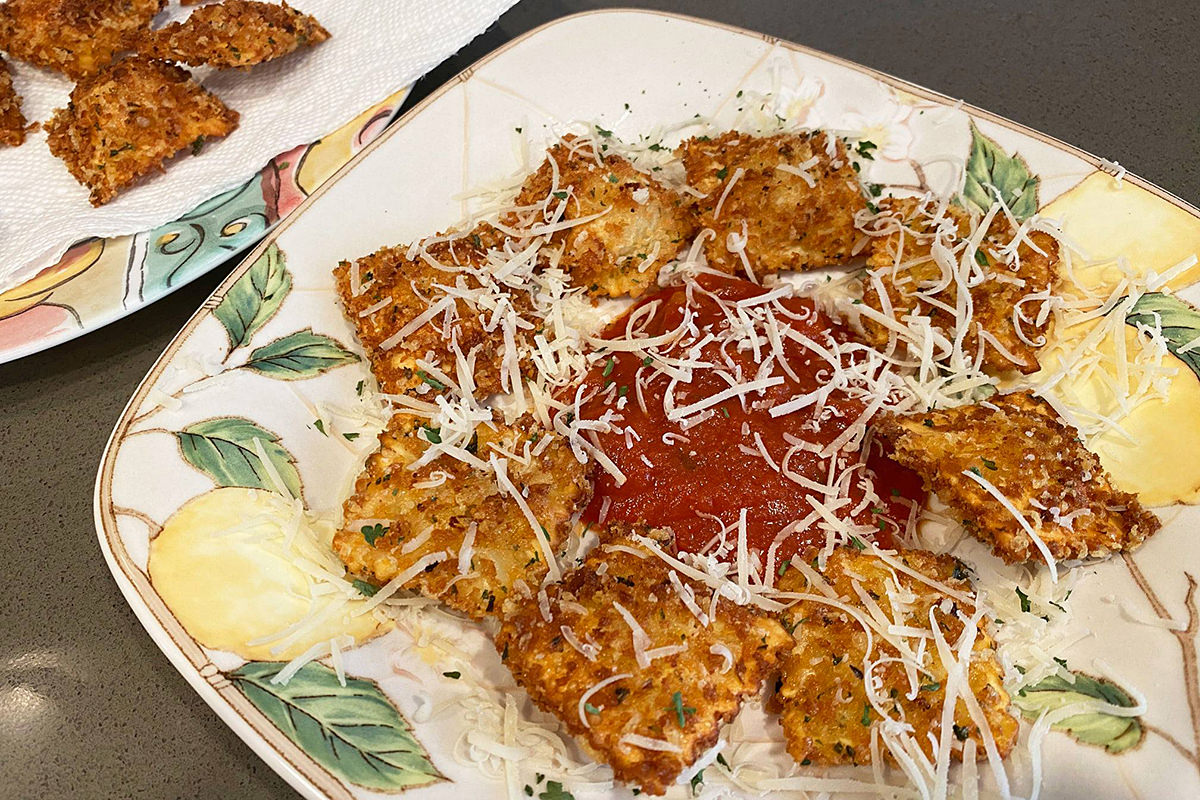 Finished T-Rav on a plate with a dollop of marinara and parmesan sprinkled on top.
