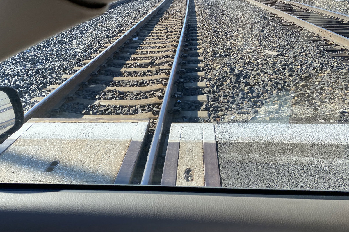 The view of railroad tracks out my passenger-side window.