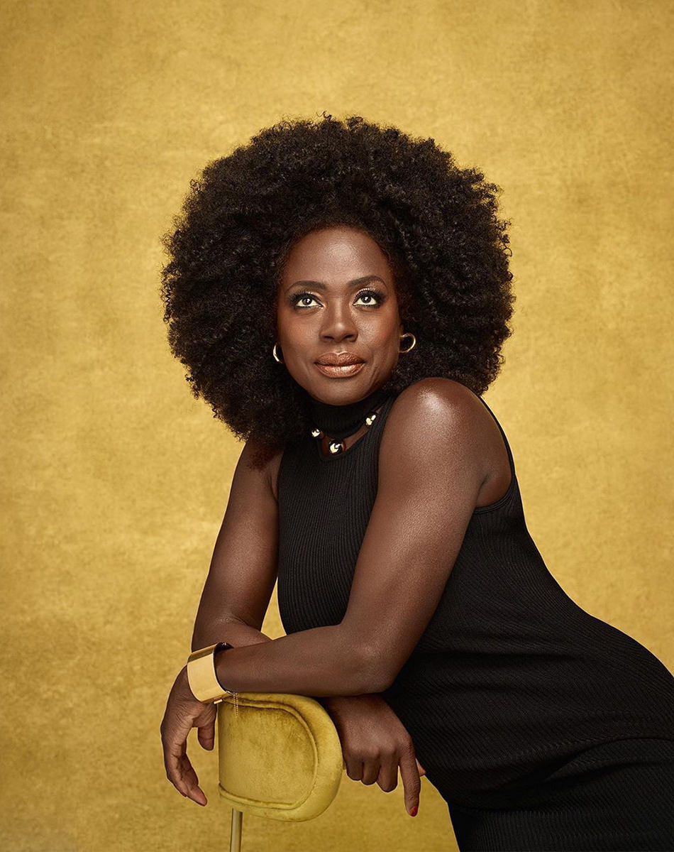 Viola Davis dressed in black shot in front of a gold background looking gorgeous as she looks upward.