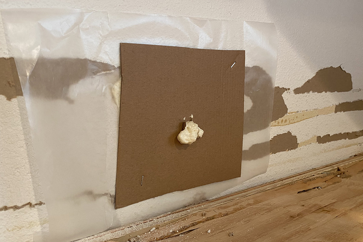 Foam spilling out of my cardboard forms stapled on the wall.