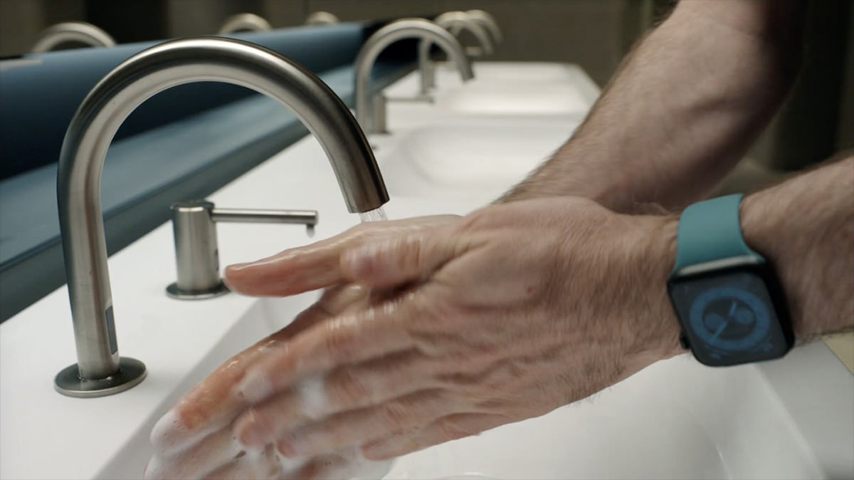 Kevin washing his hands with an Apple Watch on his wrist.