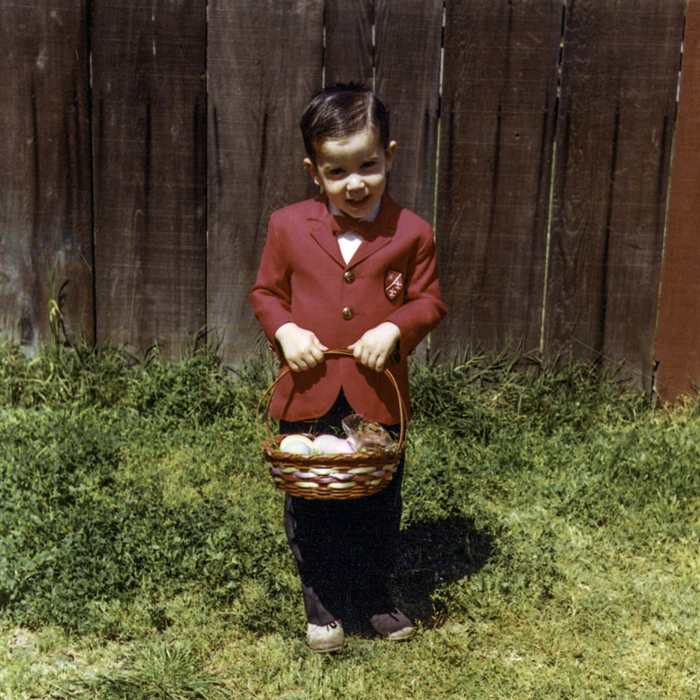 Young me with an Easter basket in the back yard with green grass and a fence behind me.