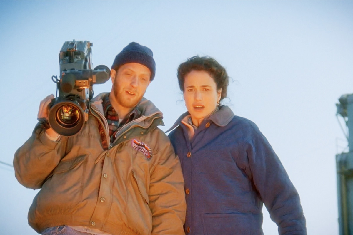 Andie MacDowell and Chris Elliot looking down the cliff at the explosion, which is reflecting on them with an orange glow.