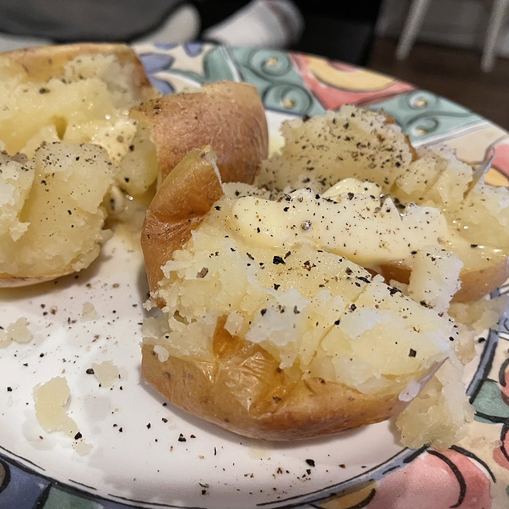 Baked potatoes on a plate with butter and ground black pepper.