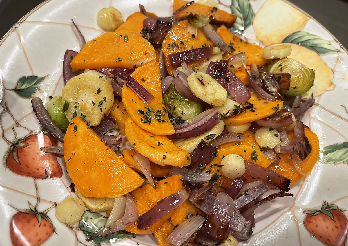 A plate with roasted sweet potatoes, turnips, brussel sprouts, and onions.