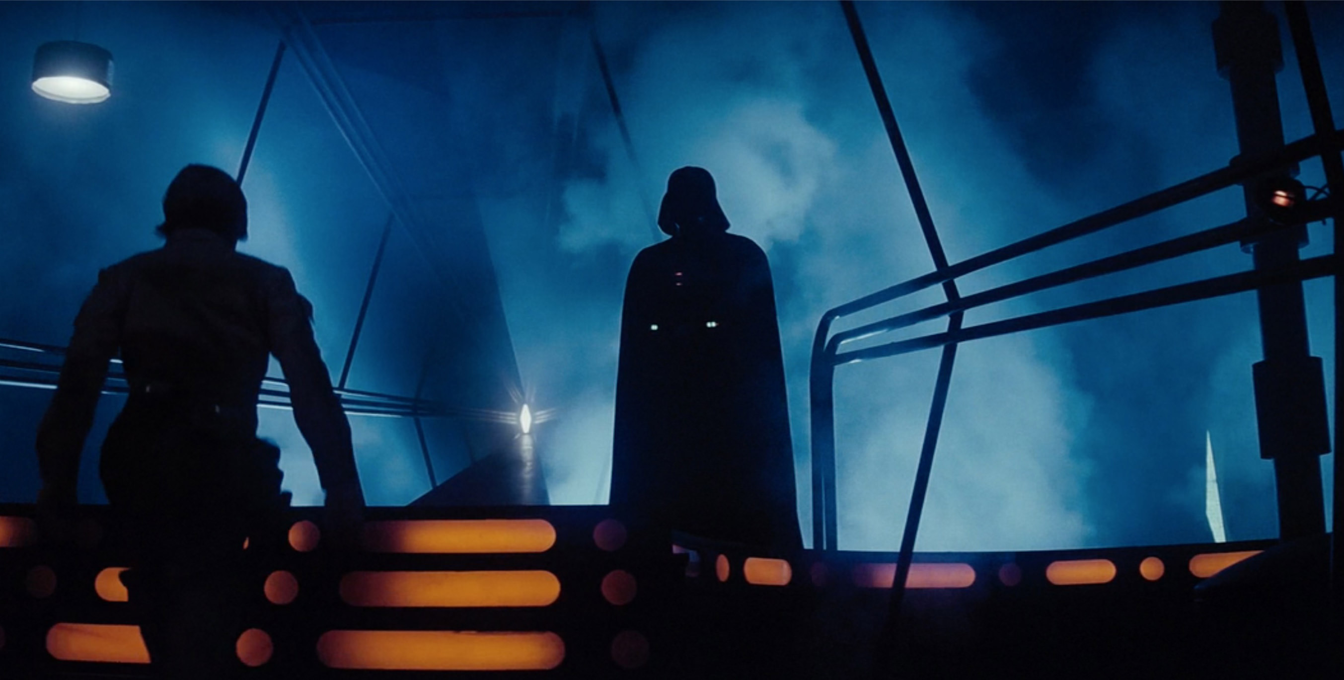 Darth Vader stands menacingly in the shadows while luke approaches to battle!