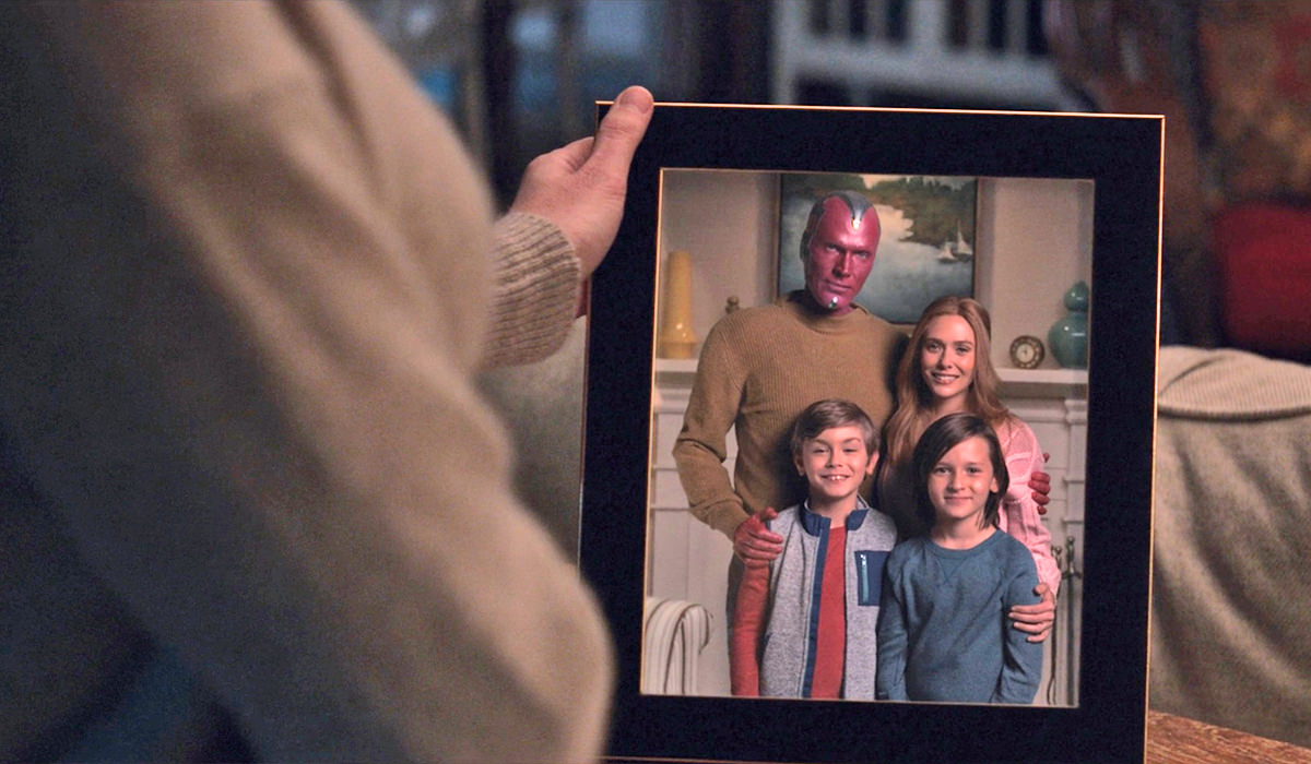 The Vision holding a photo of Wanda's created family.