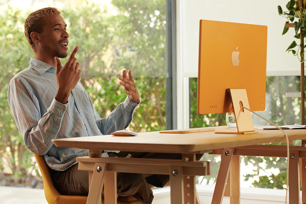 A guy talking on an iMac camera... the Mac is a beautiful yellow color.