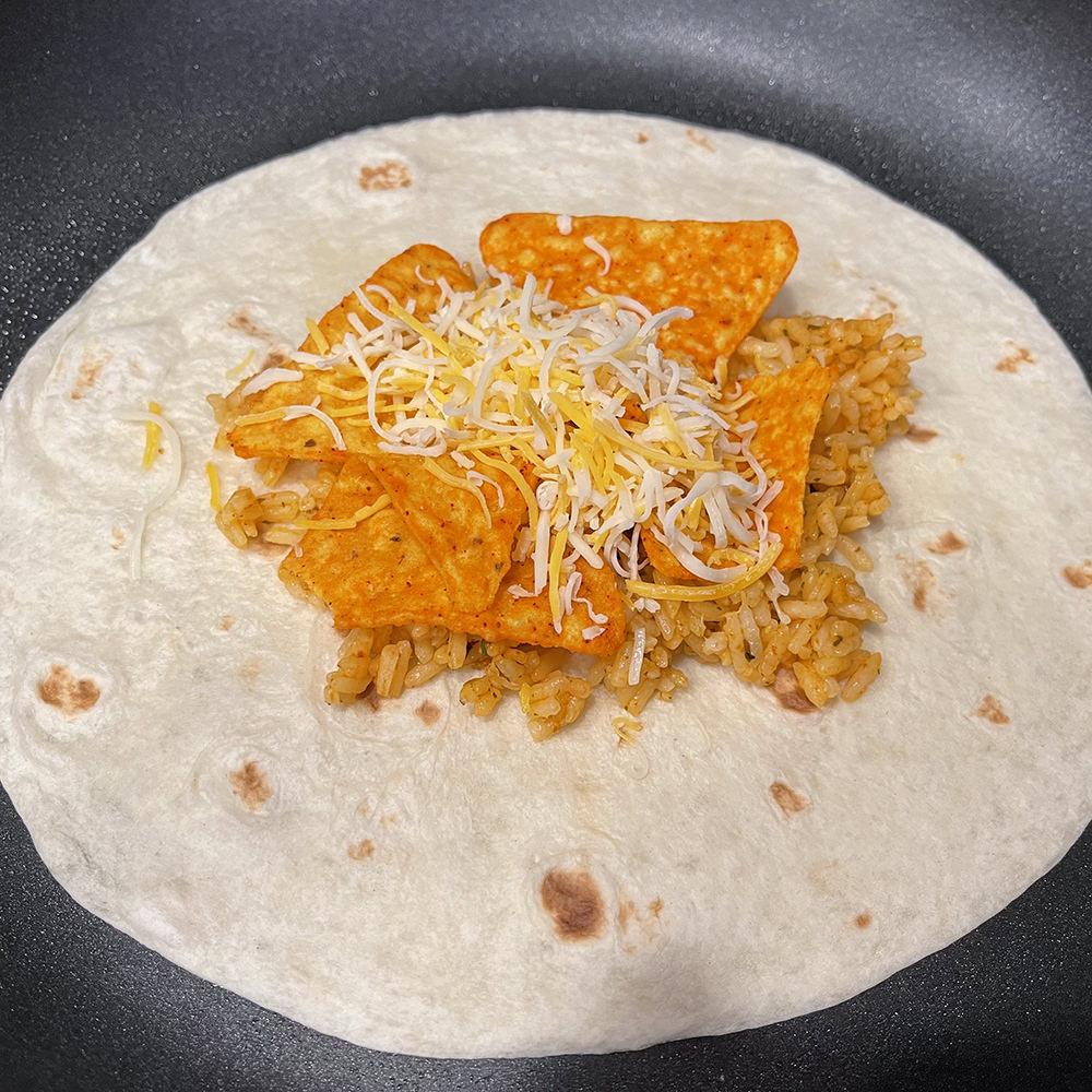 A tortilla in a pan with rice, Doritos, and cheese.